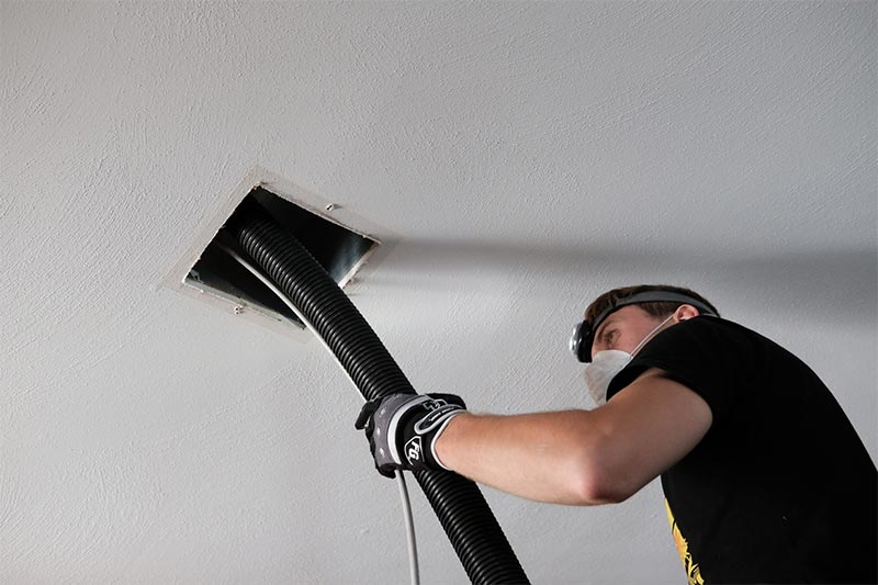 man in a black t-shirt cleaning out air vent with a black hose